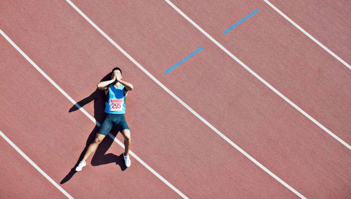 Male track athlete laying on track with hands covering his eyes looking disappointed.