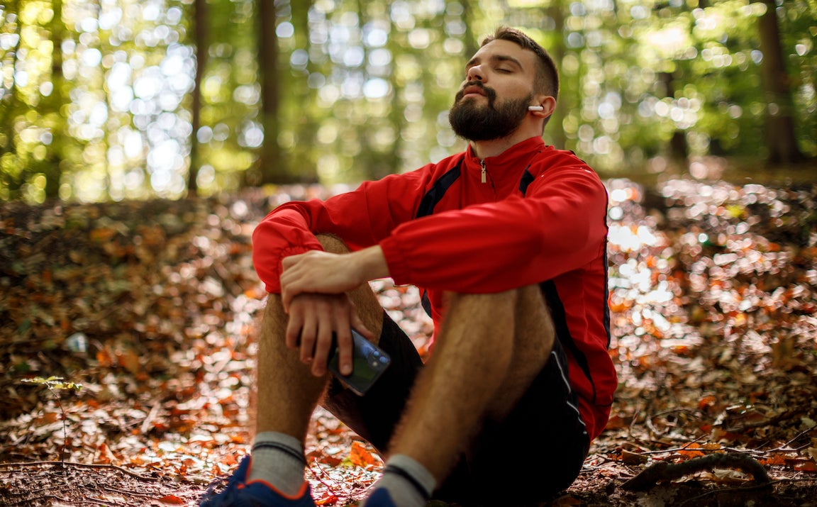 Portrait of relaxed young man with bluetooth headphones in forest.
