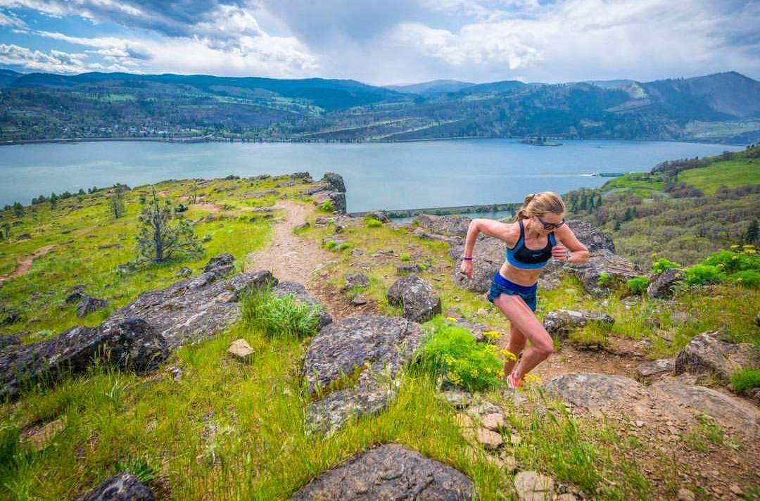 Keely corriendo por un sendero con vistas a un lago.