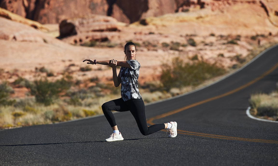 Woman runner training, warm up exercise on a long road.