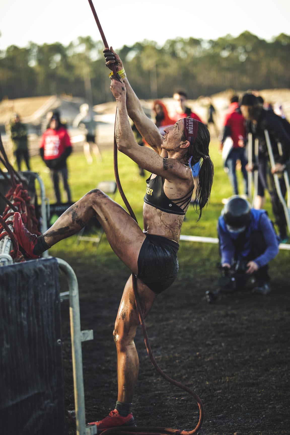 Nicole Mericle trepando por una cuerda en una competencia de obstáculos al aire libre.