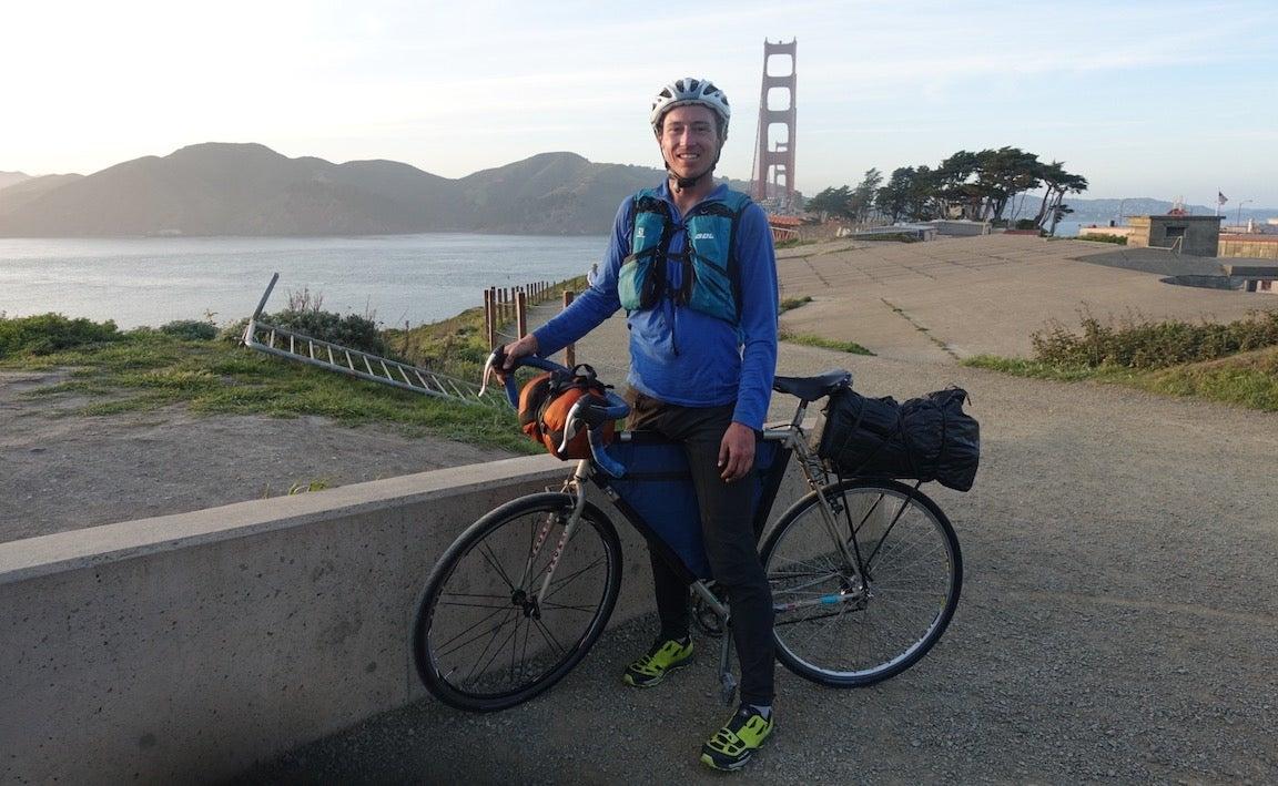 Hombre posando con bicicleta con el puente Golden Gate detrás de él.