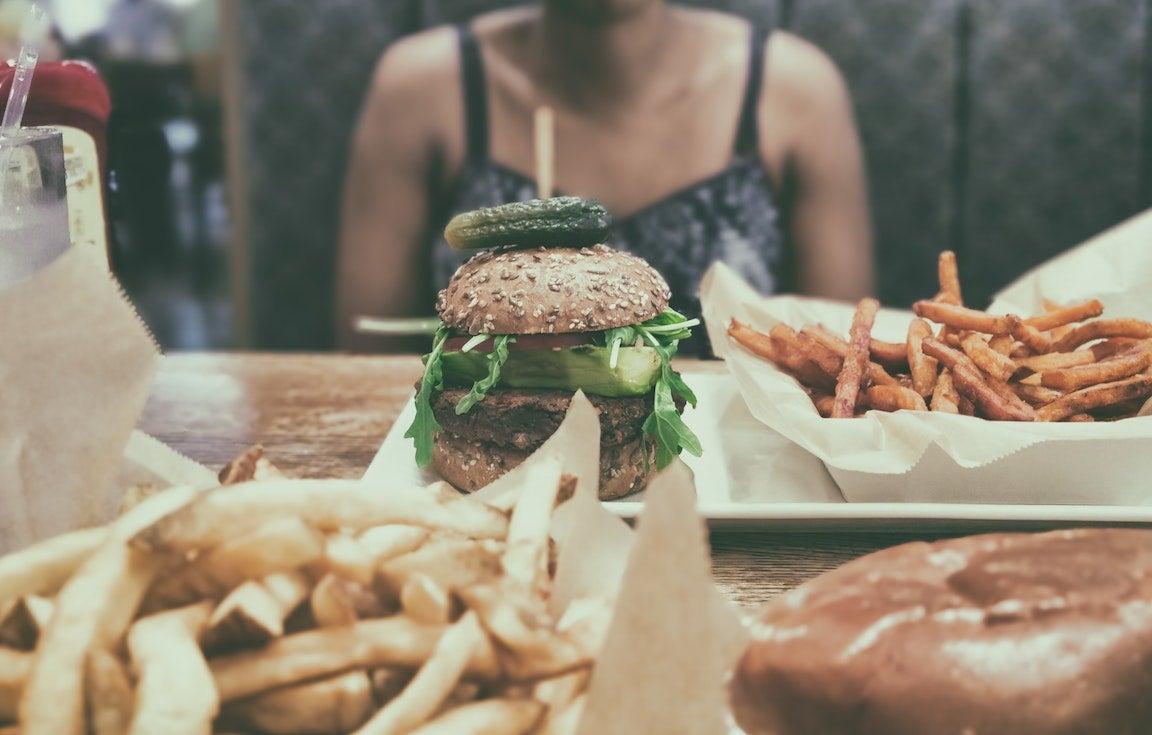 Grupo de personas en busca de comida americana, sentados a la mesa.