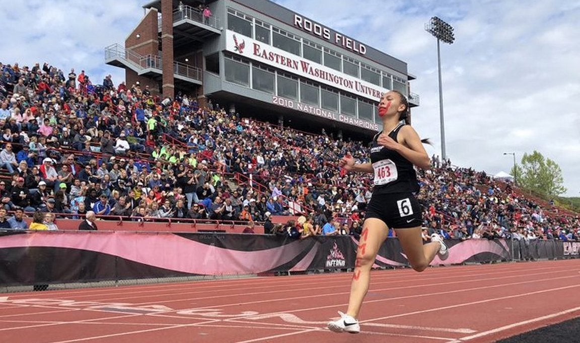 Girl crossing finish line in first place at high school state track meet with a red handprint painted over her mouth.
