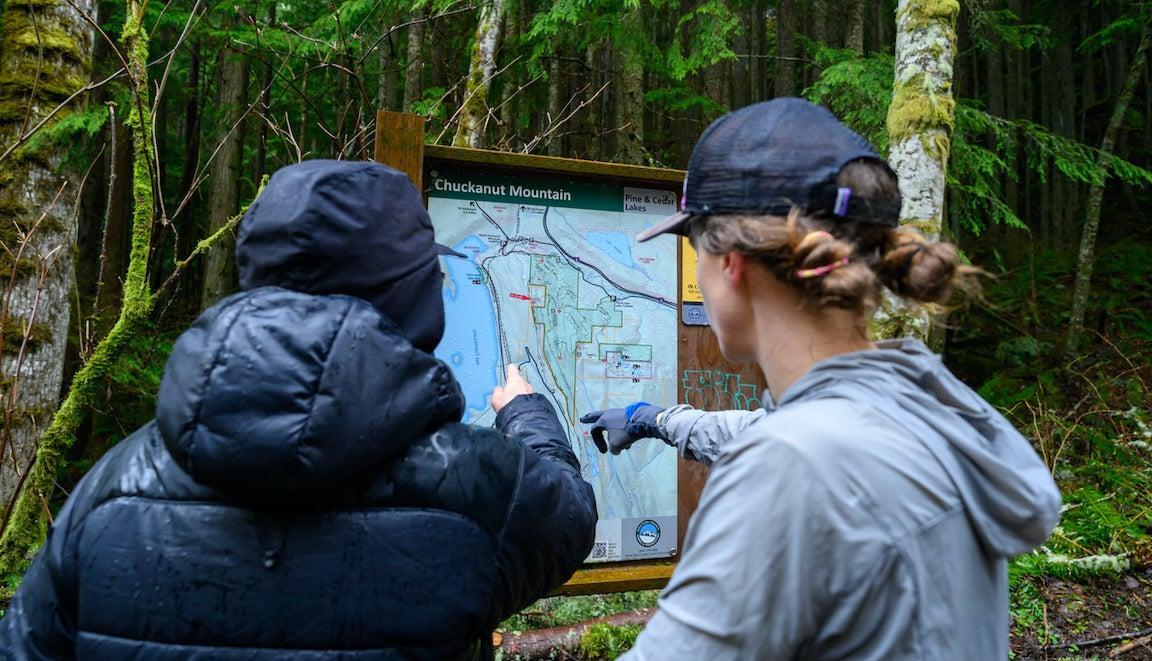 Dos mujeres mirando un mapa de senderos en un exuberante bosque verde.