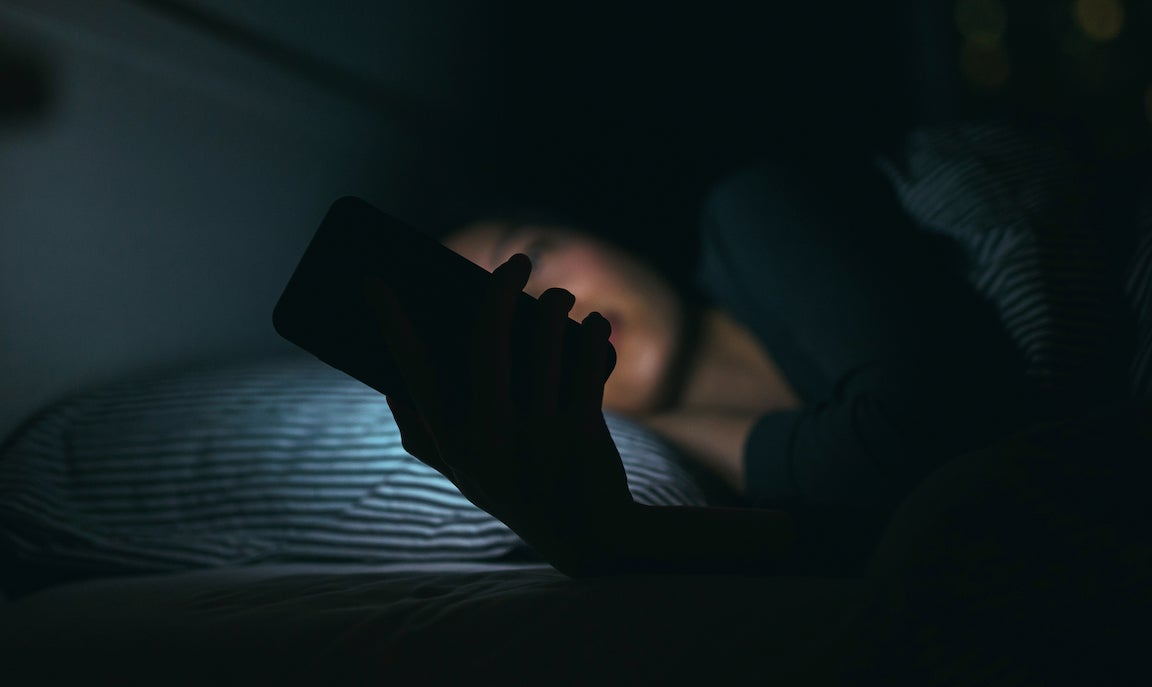 Woman unable to sleep looking at phone in bed.