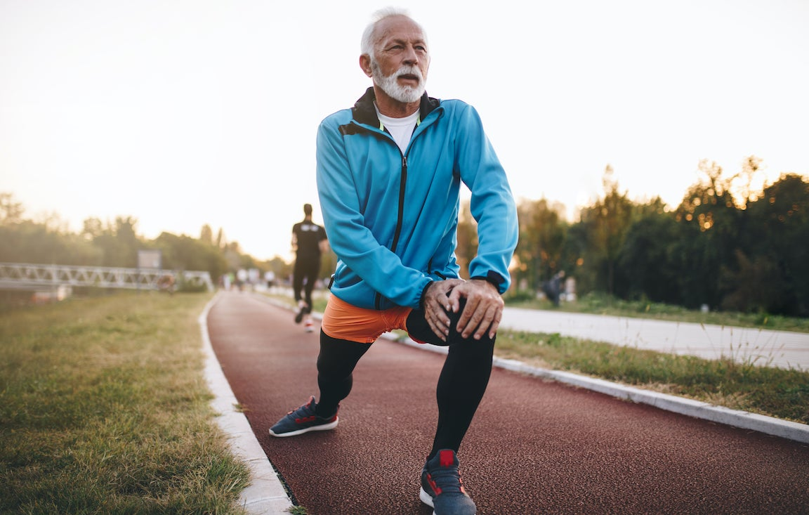 Hombre mayor que se extiende sobre una pista con la mirada centrada en la distancia.