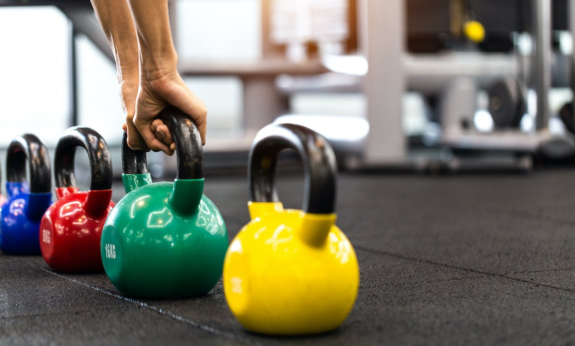 Woman in exercise gear standing in holding dumbbells during an exercise, in gym.