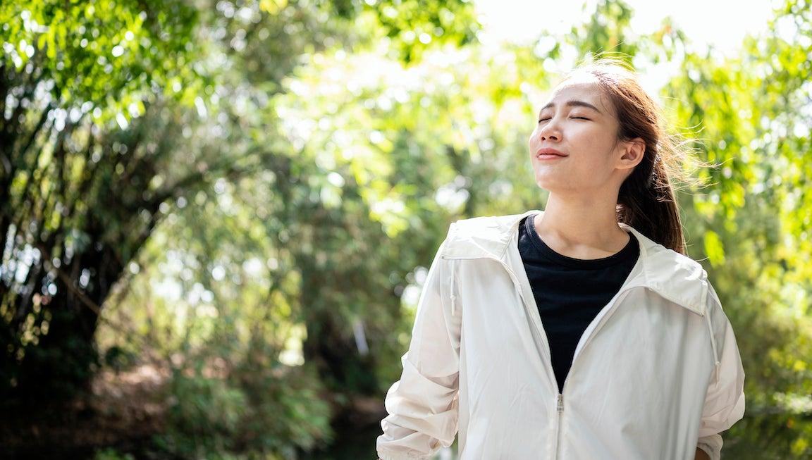 Deporte mujer relajante al aire libre después de hacer ejercicio en un parque de la ciudad.  Respira con los ojos cerrados.
