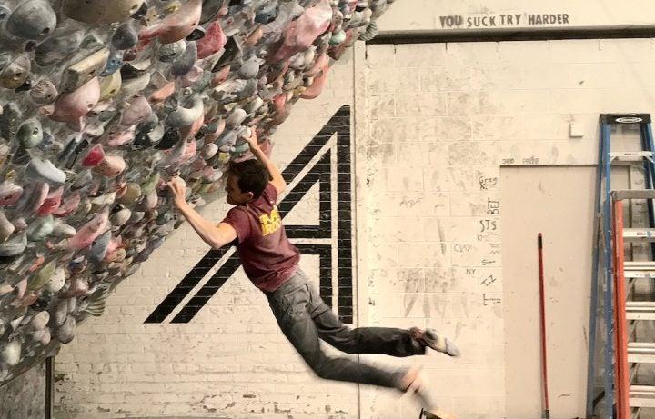 Adolescente practicando escalada en roca en un gimnasio de escalada.