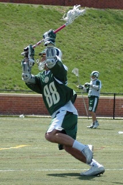 Niño con uniforme de lacrosse verde y casco jugando lacrosse.