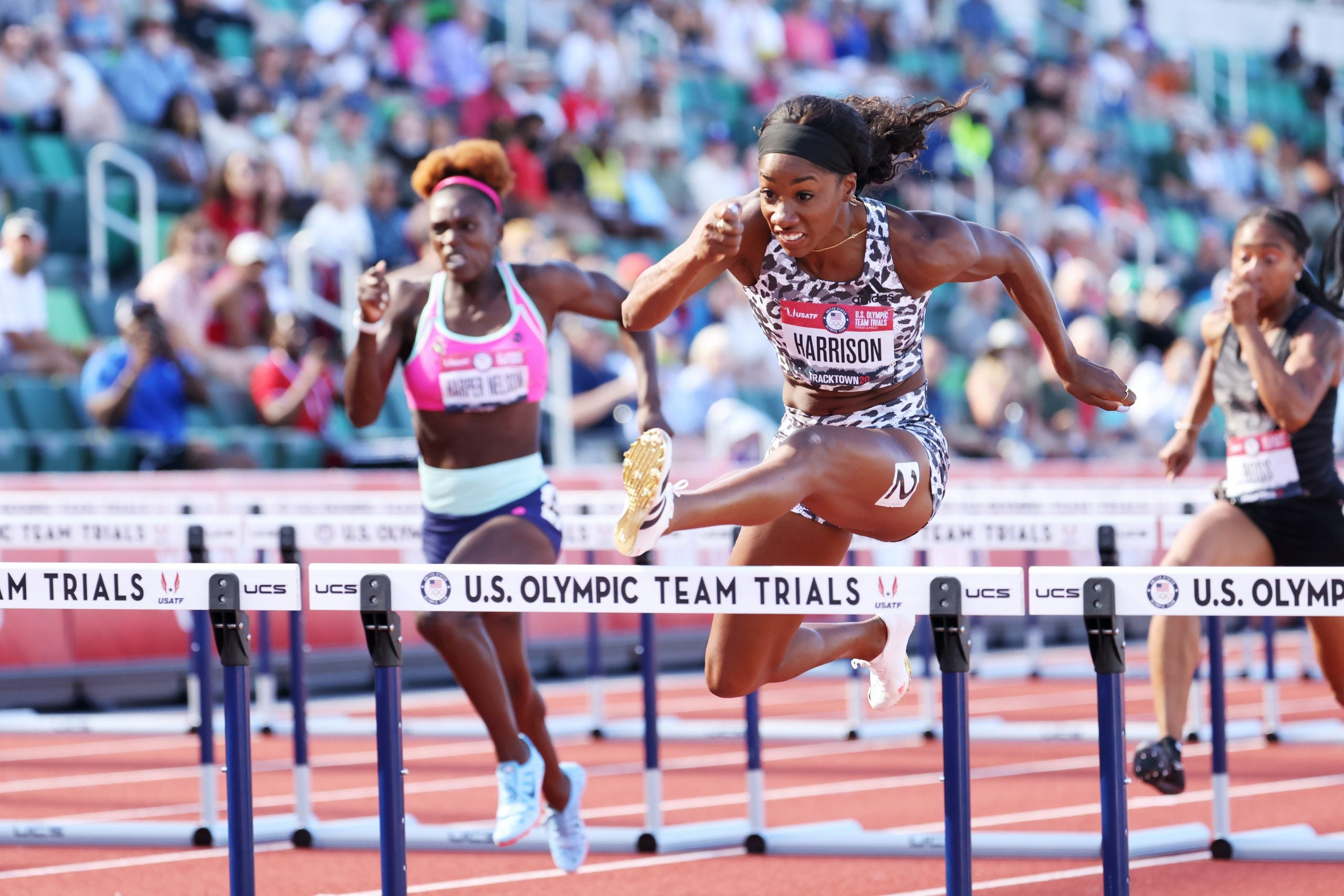 Keni Harrison leaping over a hurdle in the 100m hurdles.