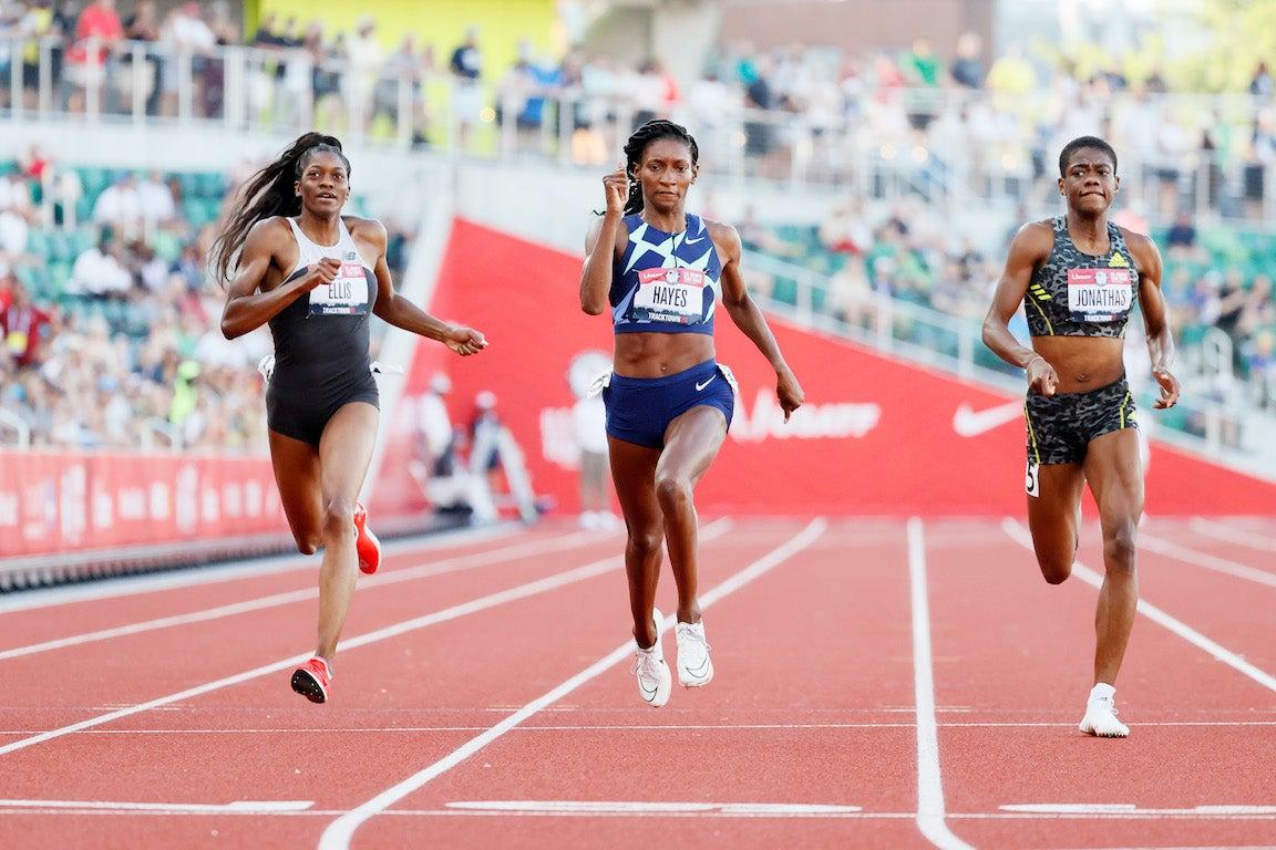 3 women cross finish line in 400 meter race on track.