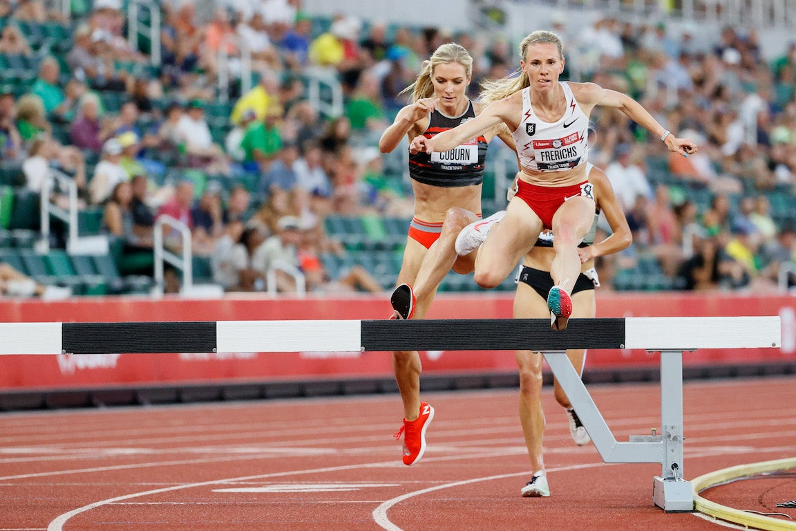 Lead women Emma Coburn and Courtney Frerichs leaping over a steeple in the women's steeple chase final in the Olympic Trials.