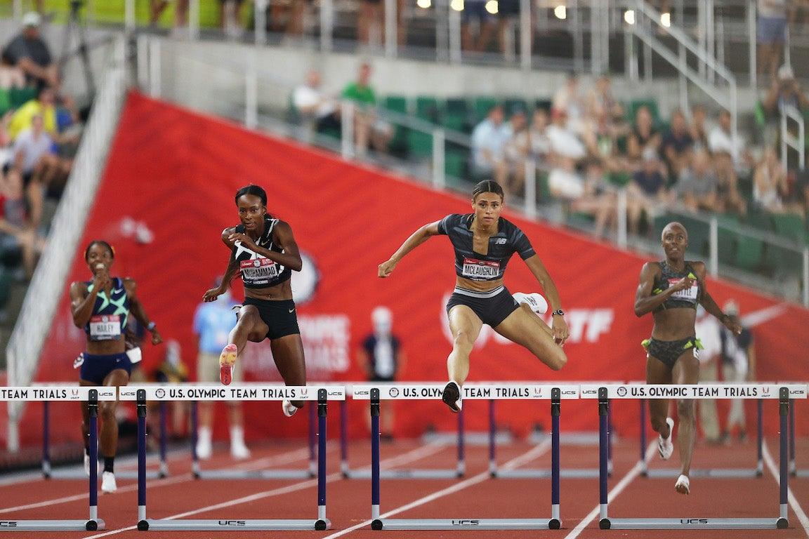 Women in 100 meter hurdles at Olympic Trials leaping over hurdles.