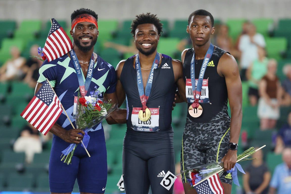 The men who qualified for Tokyo 2020 in 200 stand on a podium with medals.